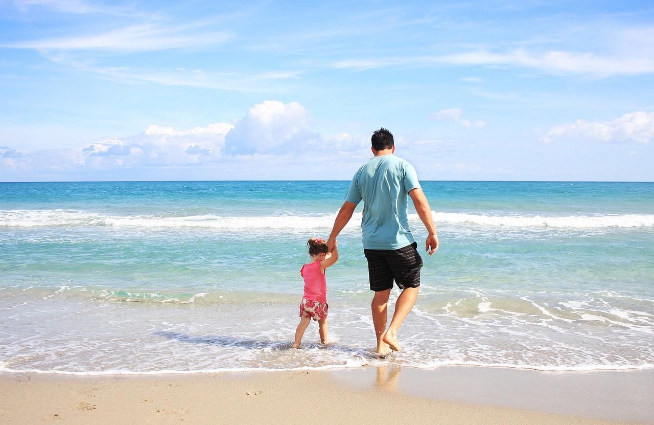 Pai Andando Na Orla Da Praia De Mãos Dadas Com Filha Pequena. Menina Está Pulando Ondas Enquanto Pai Esta Despreocupado Por Ter Trancando As Portas De Segurança Da Casa.